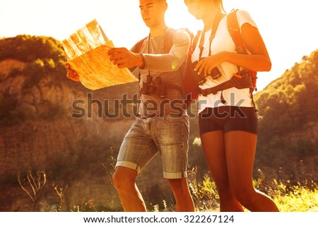 Couple hiking. Using map to get good direction - stock photo