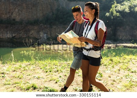 Couple hiking. Using map to get good direction. - stock photo