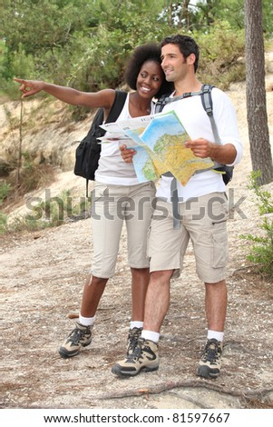 Couple hiking with a map - stock photo