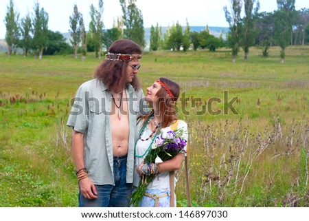 couple hippie in love with flowers on the meadow