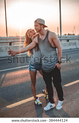 Couple hitchhiking on the road - stock photo