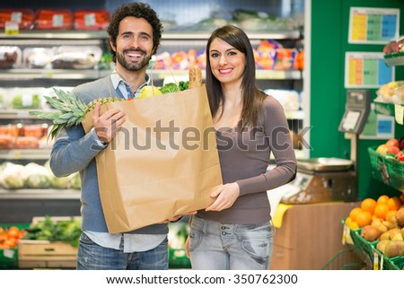 Couple holding a bag full of food at the supermarket - stock photo