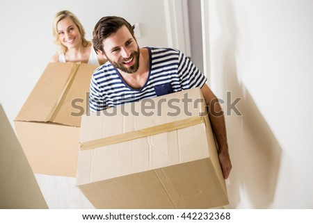 Couple holding a carton in their new house - stock photo