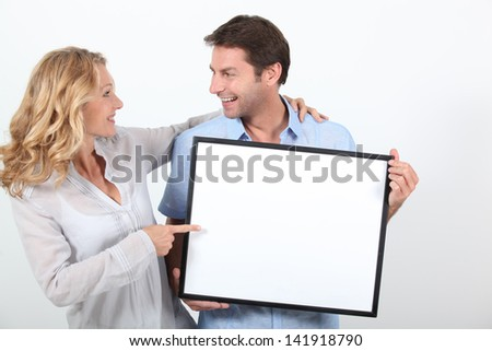 couple holding a frame - stock photo