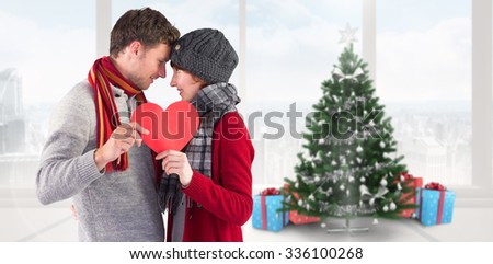 Couple holding a red heart against home with christmas tree