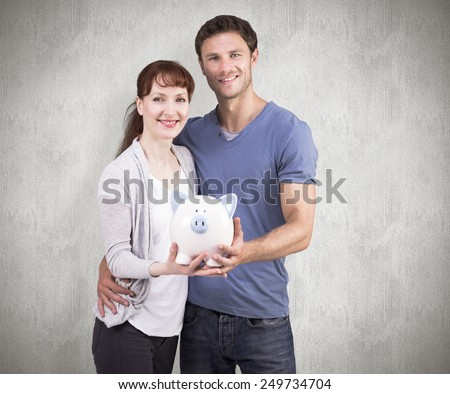 Couple holding a white piggy bank against weathered surface - stock photo