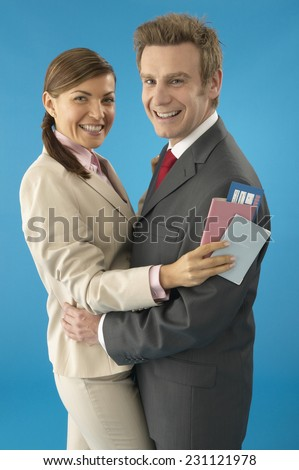 Couple Holding Airplane Ticket and Passport and Embracing - stock photo