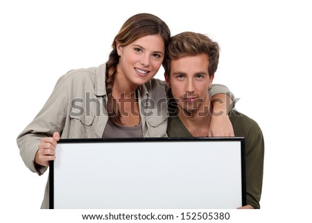 Couple holding blank picture frame - stock photo