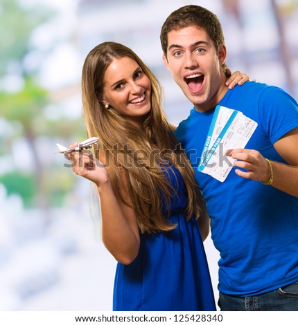 Couple Holding Boarding Pass, outdoor - stock photo
