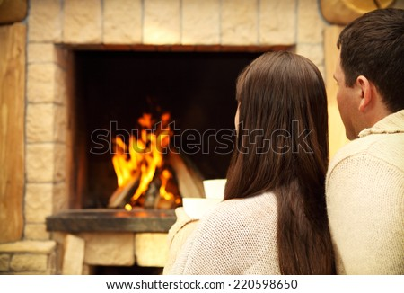 Couple holding cups with hot chocolate with marshmallows in front of lit fireplace