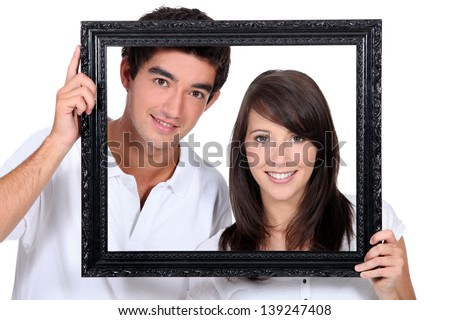 Couple holding empty picture frame - stock photo
