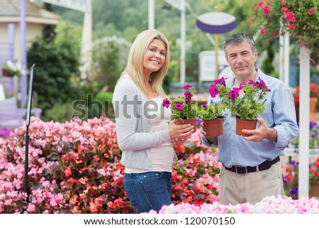Couple holding flowers while smiling in garden center