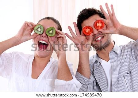 Couple holding fruit to their eyes - stock photo