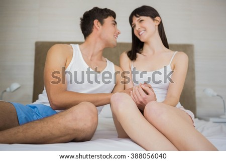 Couple holding hand while sitting on bed in bedroom
