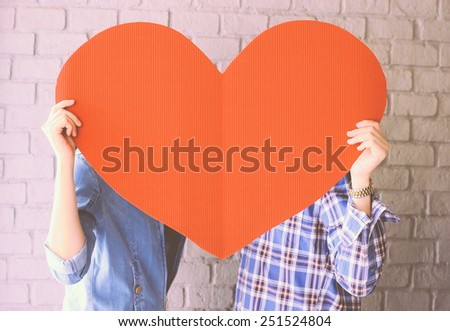 Couple holding handmade paper heart with retro filter effect - stock photo