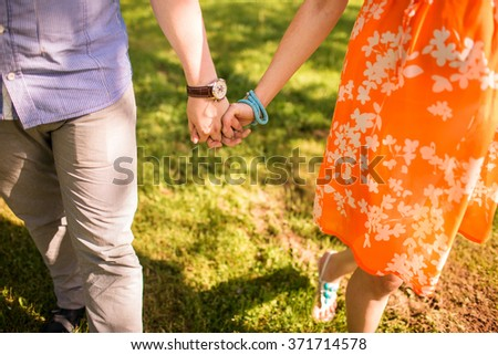couple holding hands and walking in the park. Two loving hearts have fun on green grass. Close up - stock photo
