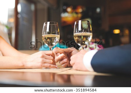 couple holding hands and wine glasses at cafe
