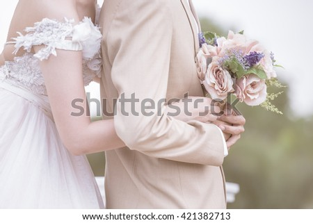Couple holding hands as a symbol of love as illustrated in weddings and paste text.