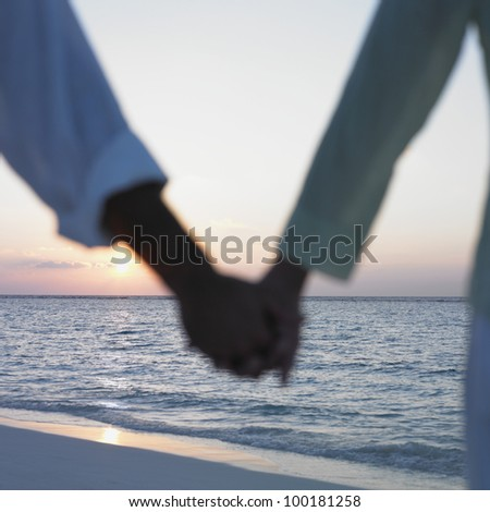 Couple holding hands at the beach - stock photo