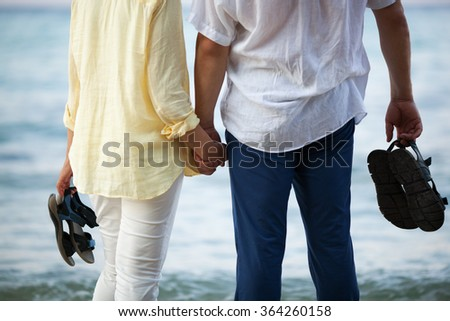 Couple holding hands at the seaside - stock photo