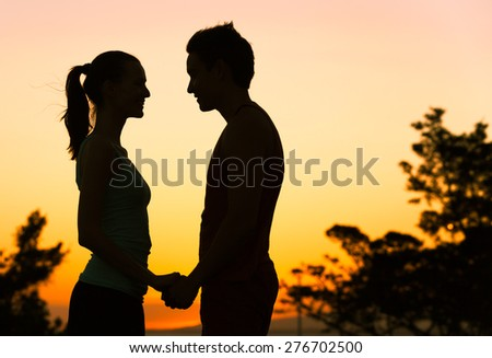 Couple holding hands during sunset.