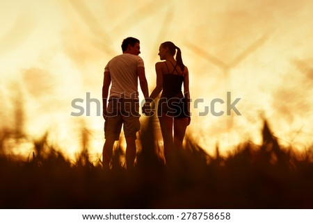 Couple holding hands in a field.  - stock photo