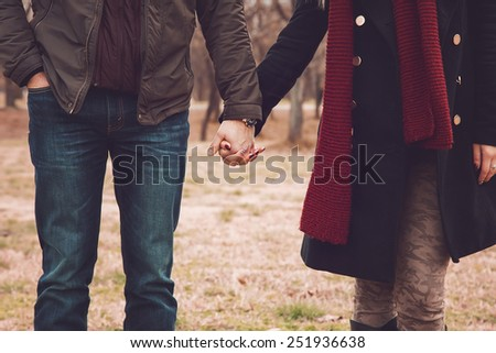 Couple holding hands in city park - stock photo