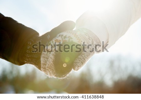 Couple holding hands in gloves in winter season at sunlight