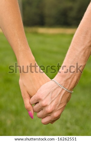 Couple holding hands in meadow close up
