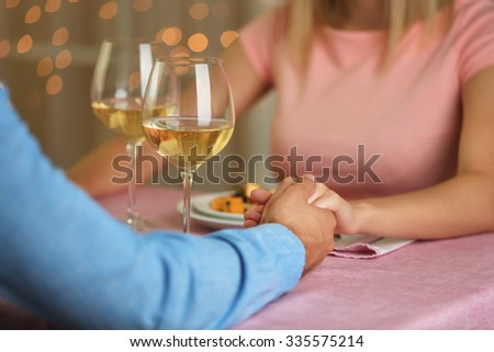 Couple holding hands in the restaurant