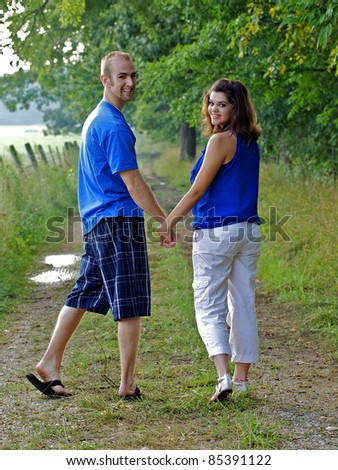 Couple holding hands looking back at photographer