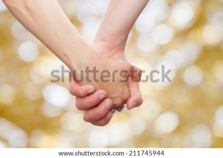 couple holding hands  on glittering background.background with bokeh defocused lights - stock photo