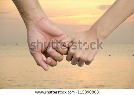 couple holding hands on sunset - stock photo