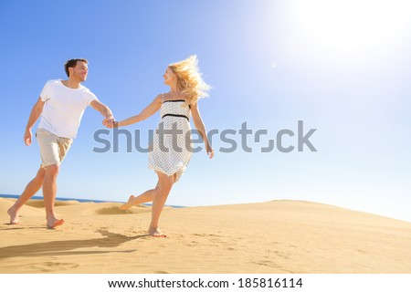 Couple holding hands running having fun under sun in playful and romantic relationship under sun and blue sky in desert. Two young lovers cheerful together on romance in summer. Joyful man and woman. - stock photo