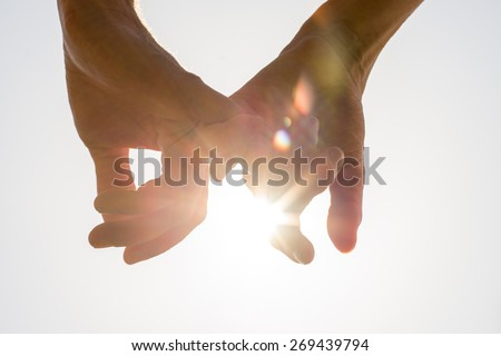 Couple holding hands towards the sun with bright sun flare between the silhouetted fingers on a pale blue sky, close up view in a conceptual image. - stock photo