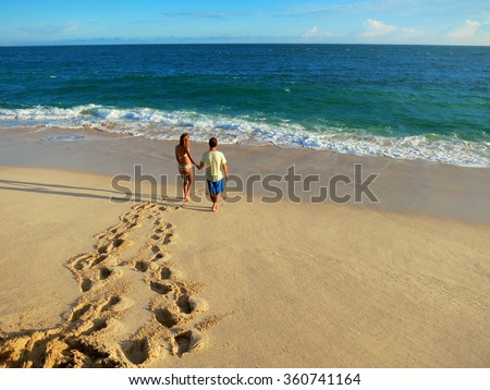 Couple holding hands walking on beach to the ocean. Man and woman in love. Footprints in the sand. - stock photo