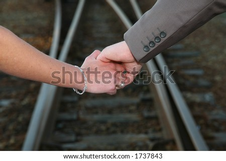 Couple holding hands with railway in background