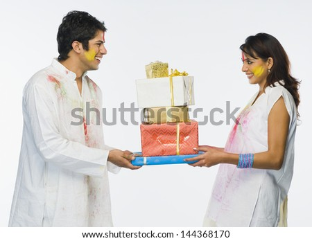 Couple holding Holi gifts - stock photo