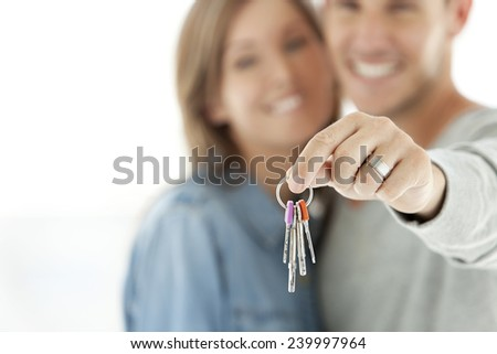 Couple holding house keys. Man and woman in their thirties. Selective focus on keys. - stock photo