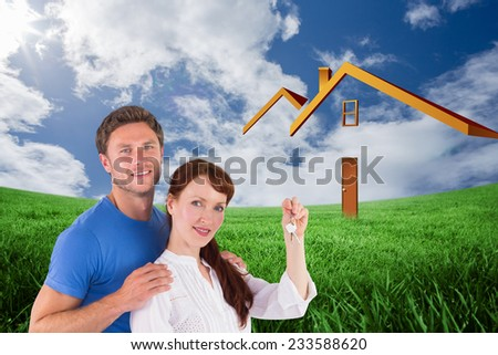 Couple holding keys to home against green field under blue sky