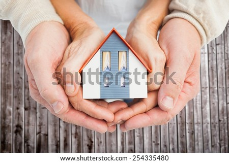 Couple holding small model house in hands against wooden planks - stock photo