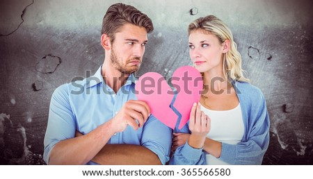 Couple holding two halves of broken heart against grey background - stock photo