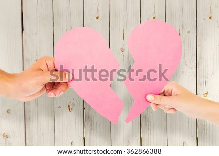 Couple holding two halves of broken heart against wooden background - stock photo