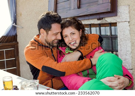 Couple hug each other and eat something at the ski resort - stock photo