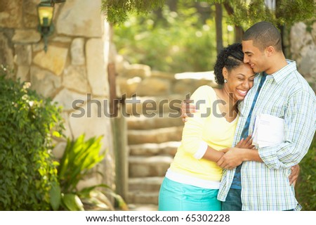 Couple hugging and laughing outdoors - stock photo