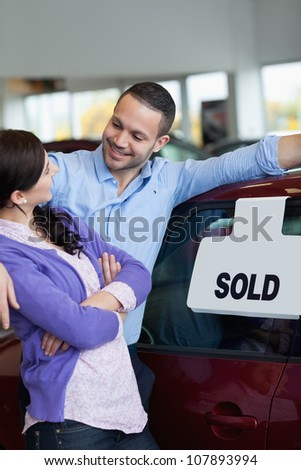 Couple hugging and looking at each other in a car dealership