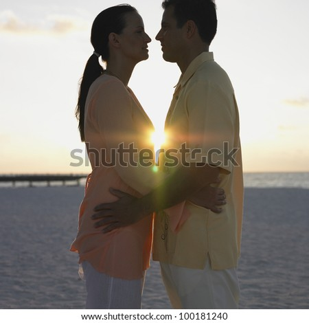 Couple hugging at the beach - stock photo