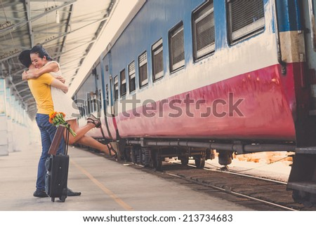 Couple hugging at the train station, girl is jumping