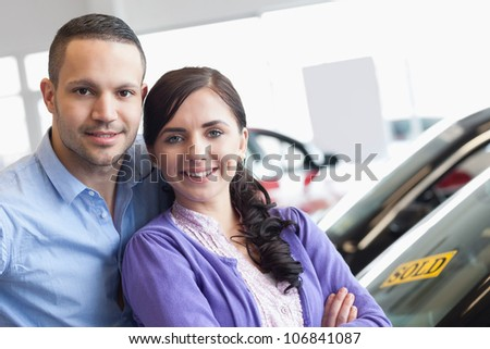 Couple hugging in front of a car in a car dealership