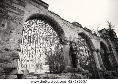 Couple hugging in love background old gates of castle. Stylish man at velvet jacket and girl in red dress in love together. Black and white photo